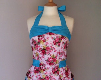 Retro apron with bow, Pink floral on a white fabric with a blue bow,  fully lined.