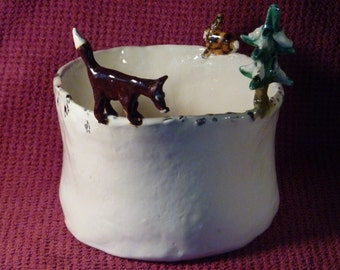 Fox chasing rabbit bowl notice the rabbit tracks. Handmade in U.S. from a lump of clay