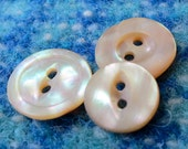 "3 vintage shell buttons, MOP,each sm and  different. 2 hole, and under 1"" ins across, with pink/peachy tones, Very sweet. HMFR14.6-14.19,"