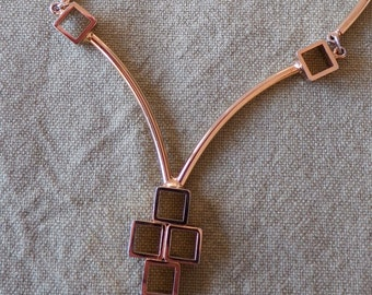 """Unusual gold toned necklace. Fixed curved bars in front, chain at back, 5 open boxed pendant in a cross shape. 18"""" ins long. SGS14.5-5.15-4."""