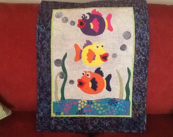 Too cute wall hanging of colorful fish would look great in the bathroom or nursery