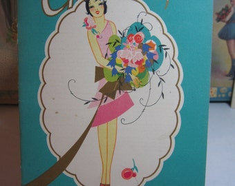 Gorgeous lady holds bouquet on August 1928 Greetings The Buzza Company Trade Booklet for Paper Sellers Greeting Cards Bridge Games etc.