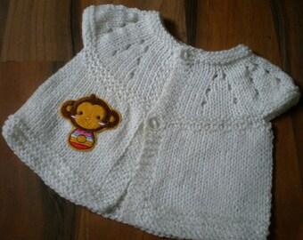 cute little hand knitted baby short sleeve top/cardigan cream with a cute monkey motif newborn