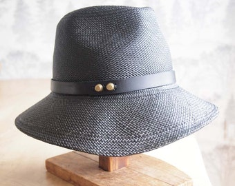 Eloise II: Assymetrical side swept brim with fedora style crown in dark midnight panama straw withdark midnight leather trim and studs