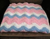 Pink blanket white and blue zigzag baby.
