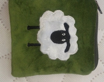 A coin purse in green velvet with a sheep on the front