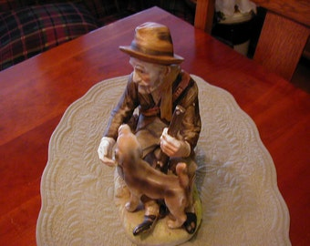 Detailed and very decorative old man and his dog hunting.This porcelain figurine is loaded with detail about the hunter and his dog.