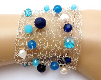 The hand-knitted wire bracelet with the beads of natural blue topaz,  blue Jade, fresh water pearls and Celestial crystals