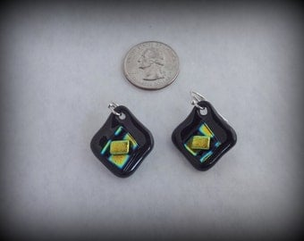 Black fused glass dangly earrings with center design highlighed by gold, black, and small shimmers of blue and green