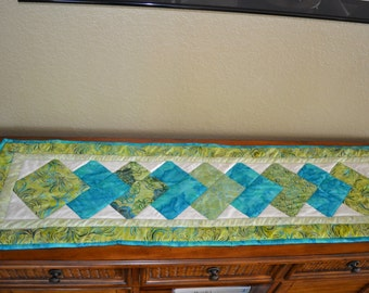 100 percent cotton batik table runner pieced and quilted in turquois blues and lime green tones of abstract florals and  geo..  1 of a kind