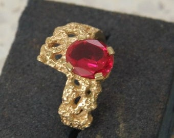 9 ct solid gold dress ring with an oval, dark pink stone