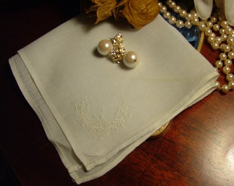White cotton ladies handkerchief has embroidered corner.