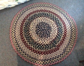Hand braided wool rug made from recycled pants suit.
