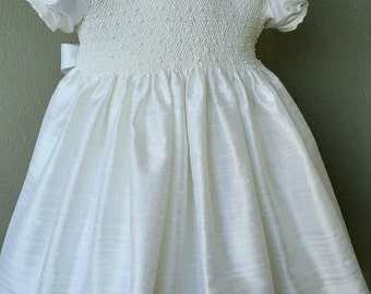 Girls custom smocked silk dupioni dress with band trimmed sleeves and pearls. Free matching bow. Two colors of your choice.
