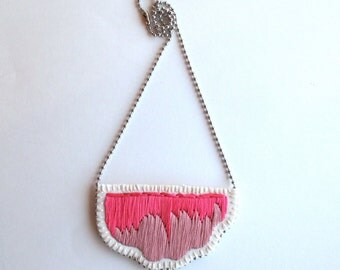 An Astrid Endeavor embroidered abstract pendant necklace in ombre colors of hot pink and dusty light pink on a silver ball chain