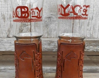 Pair of Bamco tall pilsner beer glasses, leather wrapped bases, western cattle brands rope cowboy design, stamped horses, 1950's era
