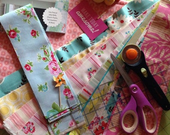 Grab Bag Girl Quilt Complete Kit With Jelly Roll Surprise Set of 20 Three Inch Strips in Colors Such as Red, Pink, Aqua and Green.