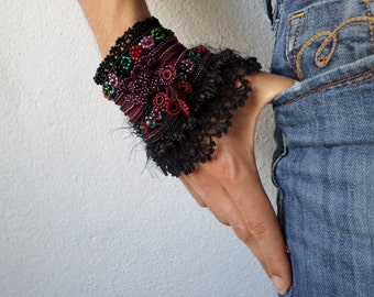 freeform crochet cuff - Asclepias Incarnata: bracelet with burgundy, purple, red, pink and green beaded flowers and black crochet lace