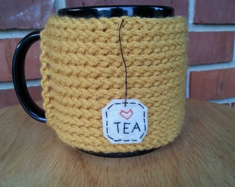 knitted tea mug cozy cup cozy in mustard yellow gold with hanging tea patch with red heart