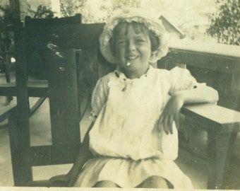 1920s Happy Girl Wearing Bonnet Sitting on Front Porch Antique Vintage Black White Photo Photograph