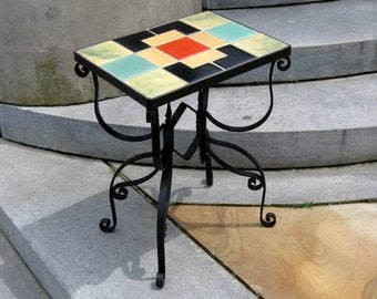 "CALIFORNIA pottery tile table , cast iron base with a "" fiesta red "" type center tile"