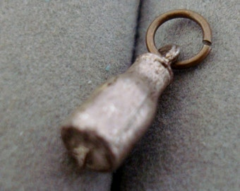 silver colored  CHARM, MILK BOTTLE is about 1/2 inch tall, it looks pewter colored.