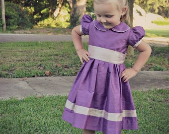 Girls custom non smocked, silk dupioni dress with ruffle trimmed sleeves and large bow/sash. Free matching bow.