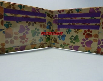handmade duct tape wallet with multi color paw prints all over it