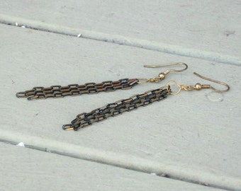 3 Gold and black glittering chain earrings.