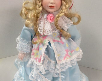 Vintage porcelain curly blond hair blue eyed doll 17 inch blue satin and lace dress  no markings used