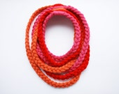 Knitted roap scarf necklace of red, pink and orange braids