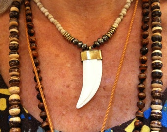 """Bone tooth pendant on Indonesian """"bone"""" glass beads, pyrite rondelles, gold plated brass discs"""