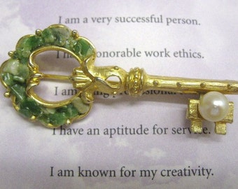 Key Brooch of Green Stones and Pearl against gold colored metal The Key to My Heart 1980s era