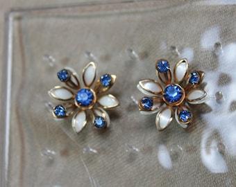 Vintage gold tone white enamel flower earrings with blue rhinestones.