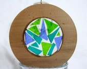 Salvaged, western red cedar round, filled with blue and green stained glass.