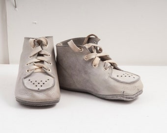 1950s blueish or grey baby shoes w perforated detail.