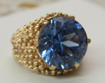 9 ct solid gold dress ring with a large, clear-blue center stone