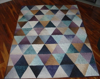 Lap size quilt in ombre fabric.