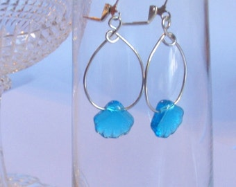 "Little tropical blue glass shells hang on a generous sterling silver hoop for an ""on the beach"" summer look.  Silver lever back wires"