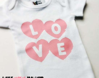 LOVE in pink hearts. Infant girl short sleeved, white onesie in 12 18 or 24 months. Black Pink Blue Green Grey Red Yellow print image