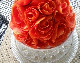 Wedding cake topper made with orange ranunculus silk flowers