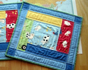 Set of two place mats for children, quilted, with primary colors, 13 inches by 14 inches. Reversible.