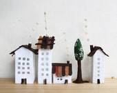 White buildings of felt, with a tree. Miniature city.