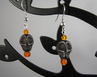 Jet black howlite skull with orange accents earrings on sterling silver wires