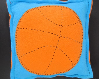 Handmade turquoise throw pillow with appliquéd orange basketball