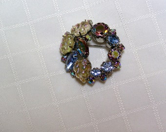 Vintage Weiss blue rhinestone and iridescent glass leaf wreath brooch.