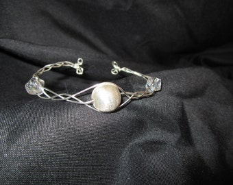 Braided wire bracelet with crystal and silver beads.