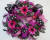 Hot Pink Metallic Deco Mesh Wreath features fun flowers, pretty ribbons, adorable feathered bird, black shiny ornaments at affordable price.