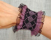 Black knitted bracelet with beads .
