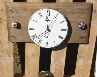 Driftwood pendulum clock with ceramic flower doorknobs